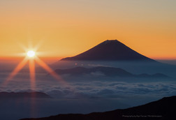 雲海に浮かぶ富士山と水平線の朝日