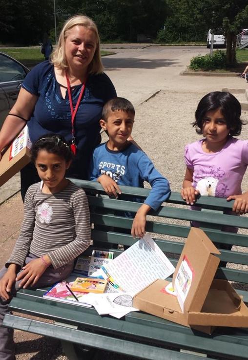 Anna von den Maltesern mit ein paar Kids, die gleich zum Gucken gekommen sind, was da in den Päckchen drinsteckt. Bald bekommen sie diese im Unterricht und können kreativ sein.