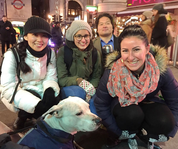 Volunteers with The Hot Choc Mob with homeless man's  street dog on London's streets