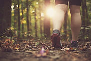 woman-walking-though-the-forest-at-sunse