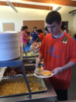 Harry's employee serving food at the Boys and Girls Club of Portland's Back to School Bash.