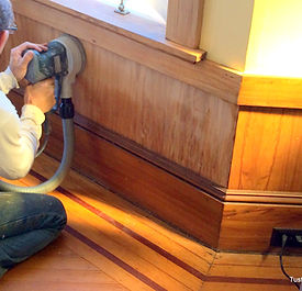 Michael Tust using tools to restore vintage gumwood woodwork in San Francisco, Ca