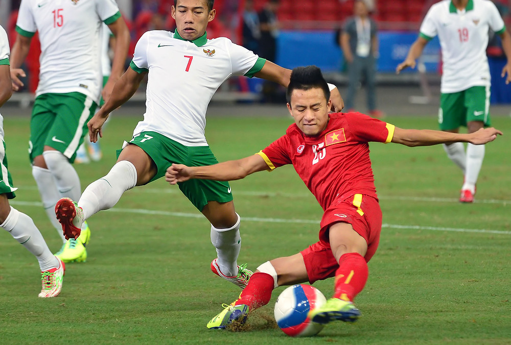 Myanmar (in white) vs. Vietnam (in red) at the packed soccer match during the 28th SEA Games