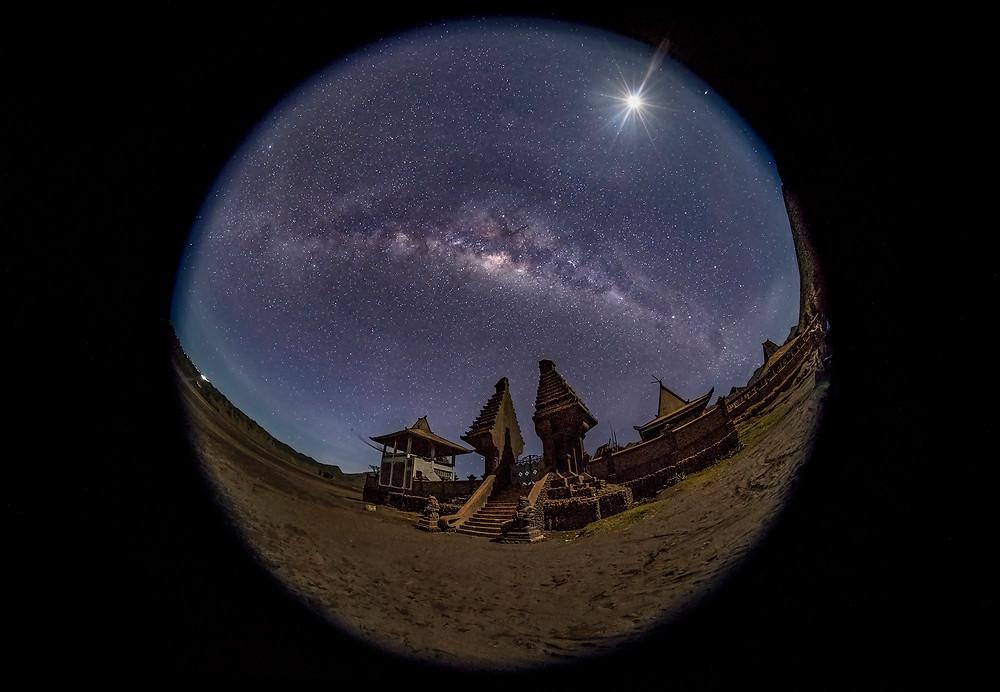 Full Milky Way and moon burst above Pura Luhur Poten temple