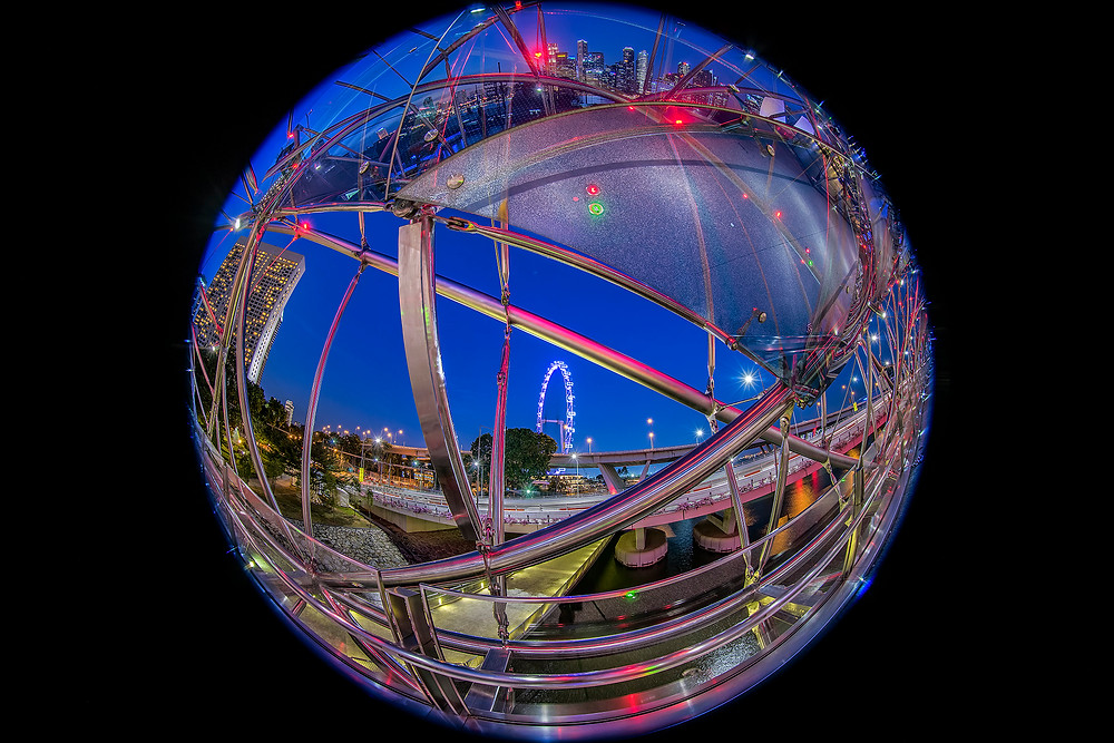 """Unusual view of The Helix Bridge """"wrapping"""" around the Flyer with the cityscape reflected at the top of the sphere"""