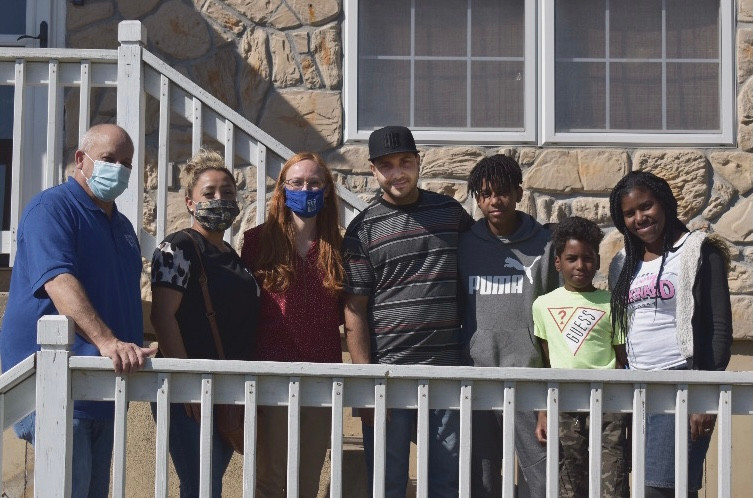 Luis, Jennifer and their family pose with their CSL support team – Jeff Sheets, Libet Ojeda and Brianna Powers outside their new home.
