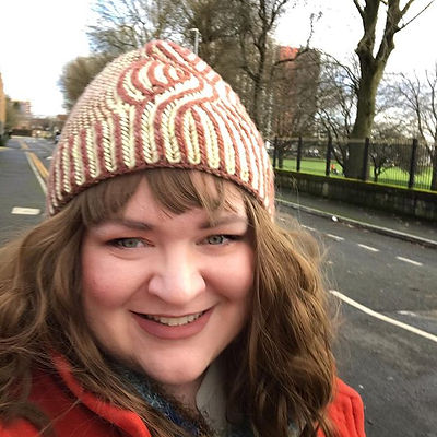 Portrait of Sam wearing a brown knitted hat.