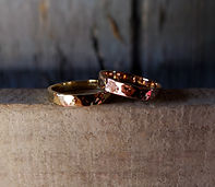 Hand crafted wedding rings in gold sitting on a piece of wood with a grey background