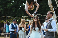 Bride being served champagne from a circus performer who is hanging upsidedown. There are guest, trees and festoon lights in the background