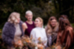 Bride and her four bridesmaids standing in a row in a forest, they are wearing autumnal colours and holding autumnal bouquets and they ae all laughing. The bride is wearing a gold crown.