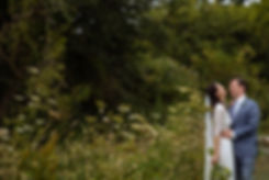 Bride and groom standing at the edge of a meadow laughing. There are trees and tall grasses in the background.