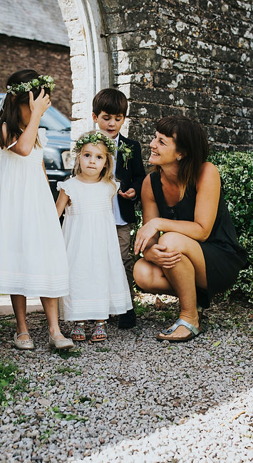 Wedding planner bending down talking to two flowers girls and a page boy just before they walk the aisle. They are outside standing in front of a wall and the flower girls are wearing white dresses