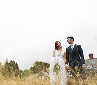 Bride and groom standing in tall grass with a stately home in the background