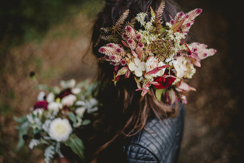 Bridal floral crown in autumnal pinks, whites and deep reds. The bride has dark brown hair, a leather jacket and is holding a bouquet in the background.