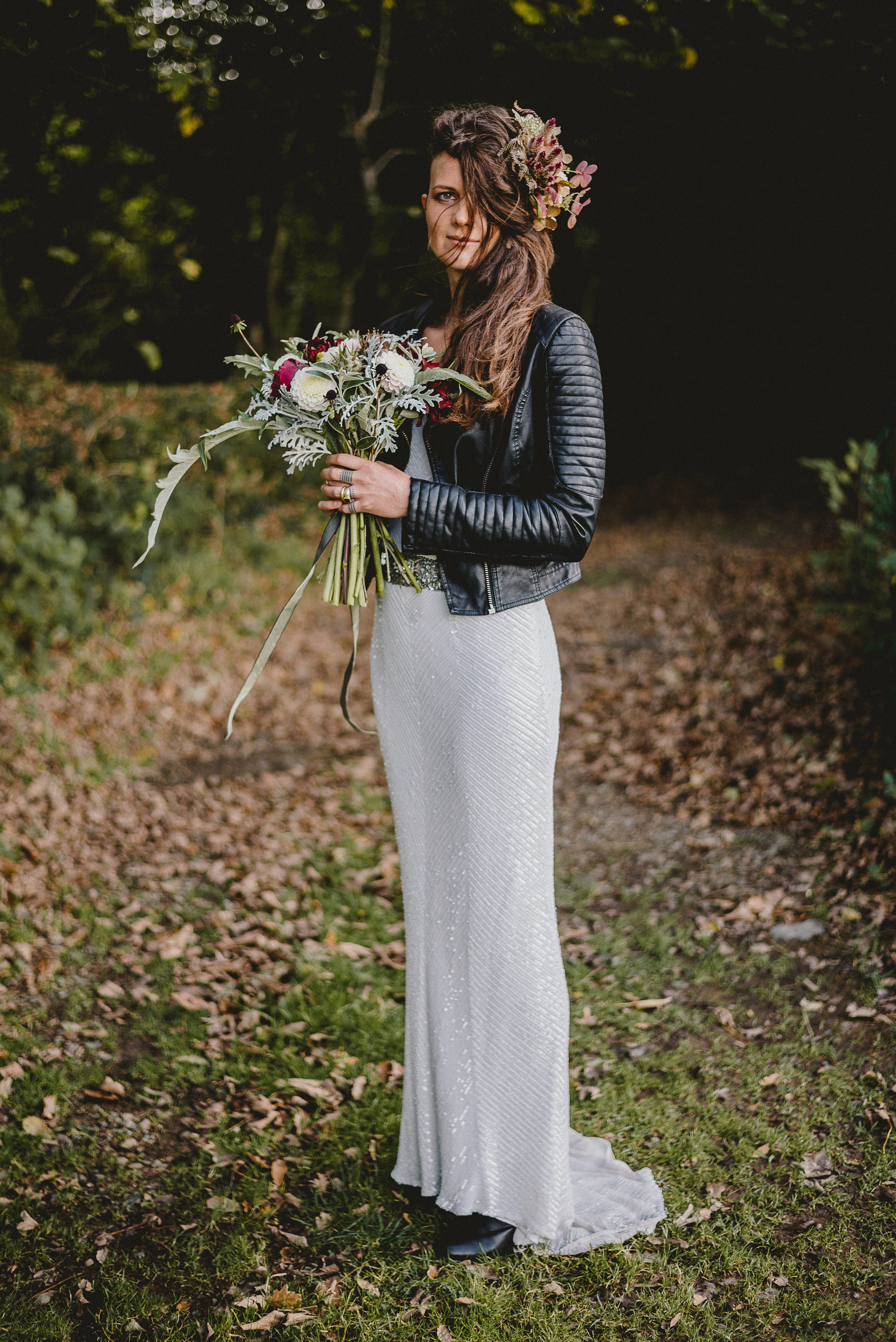 Bride standing outside holding a bouquet of flowers in whites and deep reds. she is wearing a beaded dress and a black leather jacket. she has pink wild flowers in her hair.