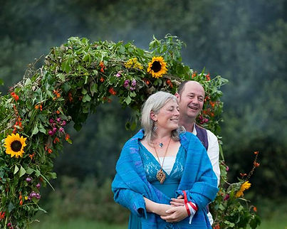 Bride and groom standing in front of a flower arch. Bride is wearing a teal wedding dress