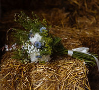Wildflower bouquet laying on  a hay bale