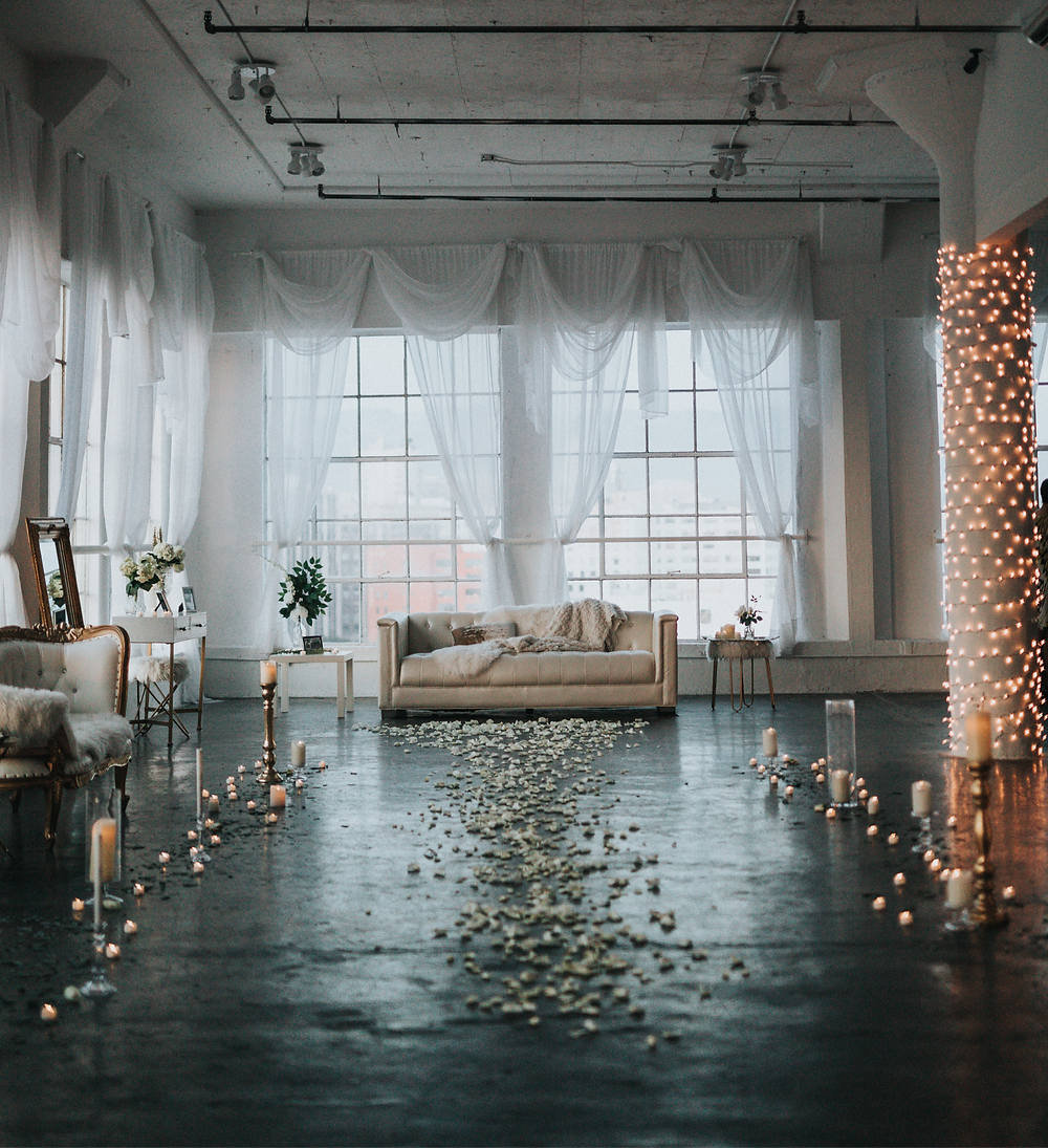 Industrial chic wedding ceremony room for intimate wedding with cream sofa's, candles and petals on the floor