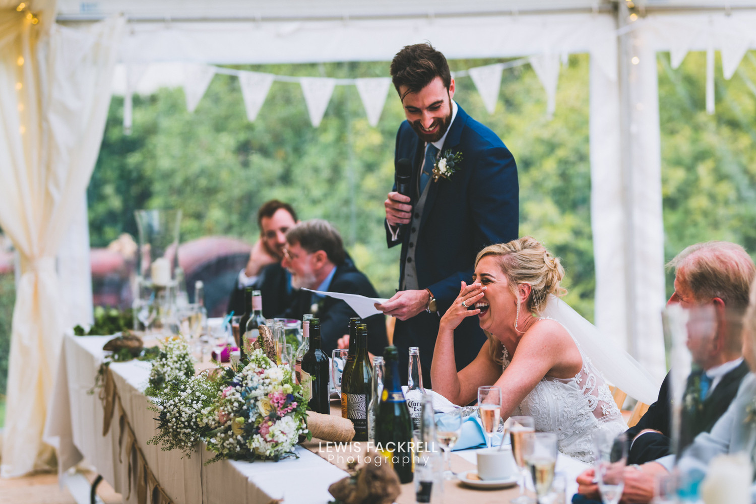 Marquee wedding reception, the top table, groom is standing giving a speach and bride is laughing
