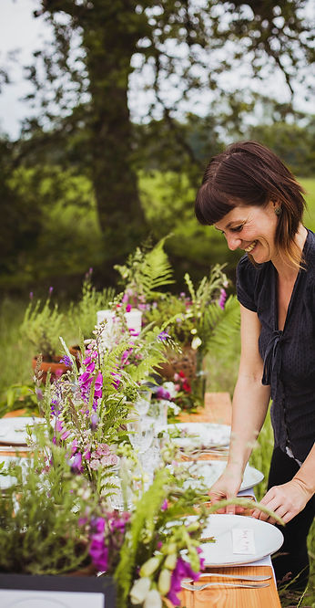 Wedding planner in meadow setting a wedding table with wild flowers