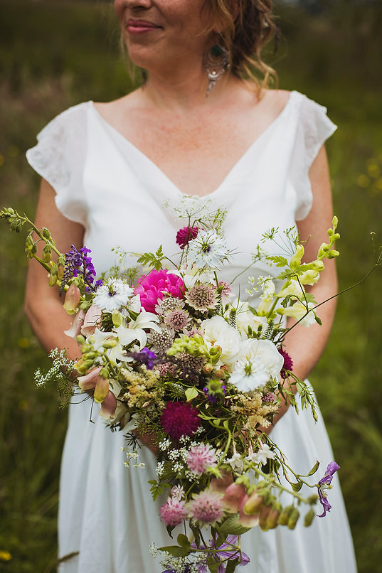 Close up of a wildflower wedding bouquet being help by a bride