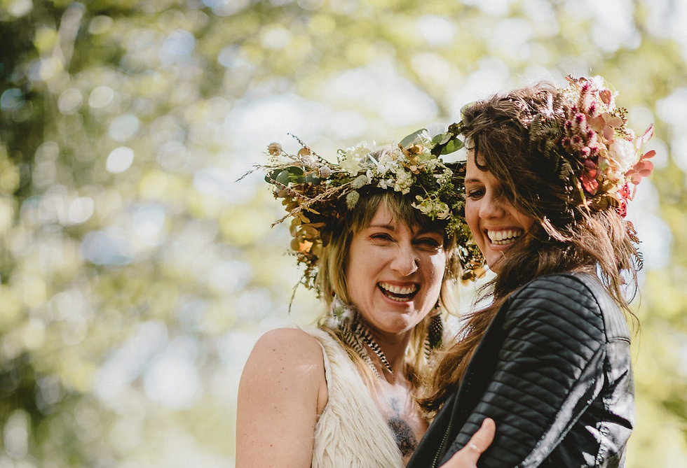 Two brides embracing and laughing. One has a big floral crwon in autumn tones and feather earings, the other is wearing a leather jacket.