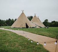 A large wedding tipi standing in a field with a matting walkway and festoon lights leading to it.