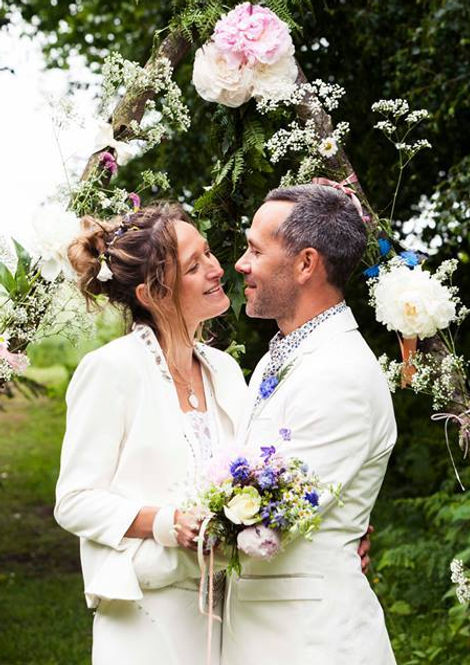 Outdoor cremony. Bride and groom standing in front of a wildflower arch, bride is holding a bouquet