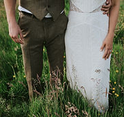 Bride and groom from the waist down standing in a wildflower meadow