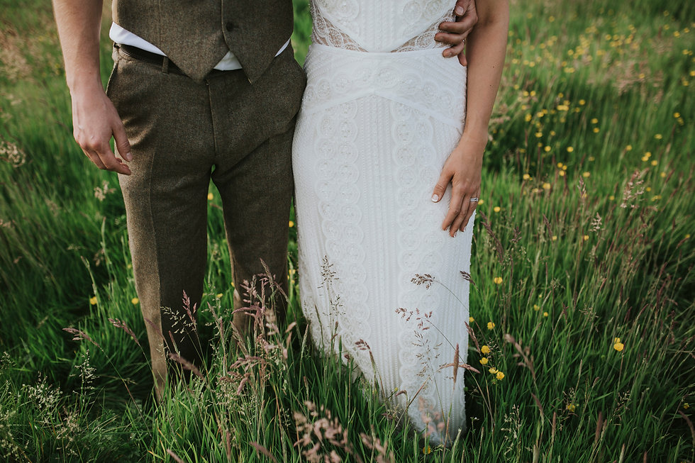 Bride and groom from waist down standing in a meadow of tall grass.