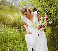 Bride carrying colourful bouquet through a meadow of tall grass