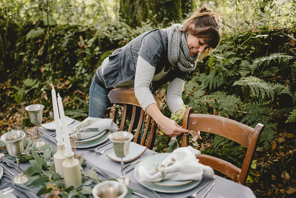 Wedding planner preparing an outdoor wedding table. She is tying flowers onto a chair and there is a forest in the background. The table linens are grey.