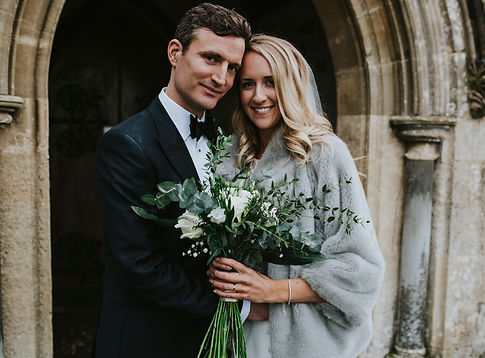 Bride and groom standing in front of a church entrance, bride is wearing a grey fur coat and holding a wildflower bouquet in whites and greens