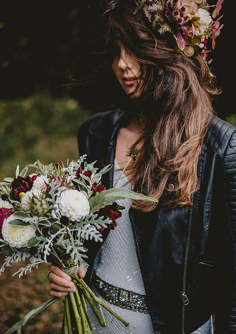 Bride wearing a beaded dress and leather jacket. Her hair is mostly covering her face and has a statement flower crown in autumnal pinks. She is holding a bouquet of white, green and deep red flowers.