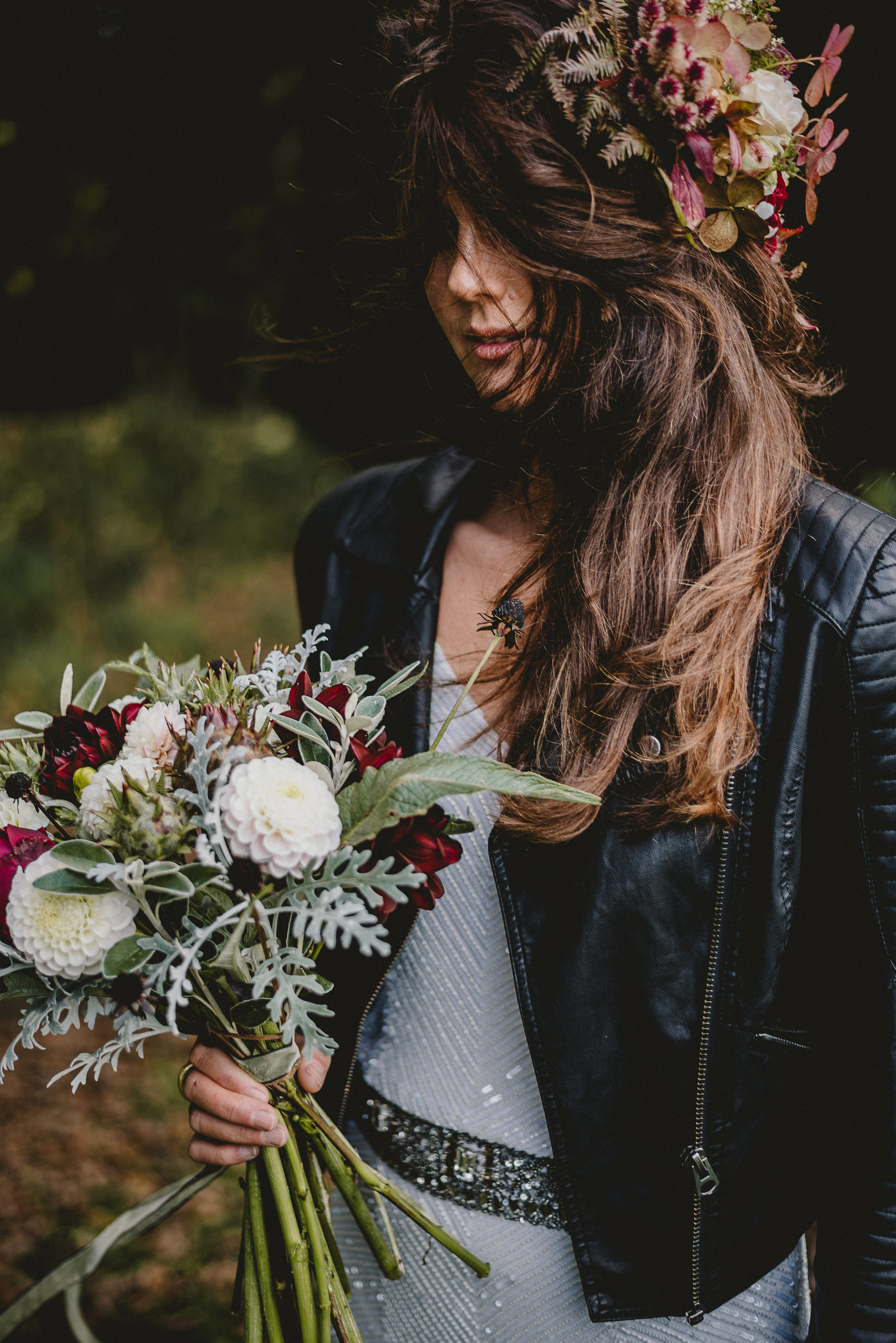 Bride holding a bouquet. She is wearing a beaded wedding dress and black leather jacket. She has a floral crown in pinks.