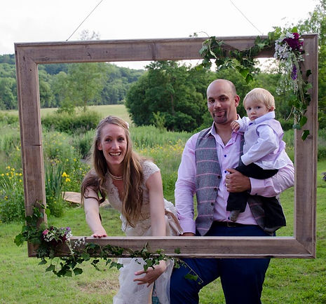 Bride and groom in the garden framed in a large wooden frame, groom is holding their son