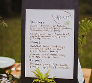 Hand calligraphed wedding menu displayed on a piece of slate on an outdoor wedding table