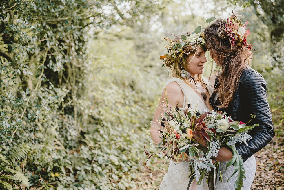 Two brides holding each other in a forest, they have big floral crowns and are holding bouquets.