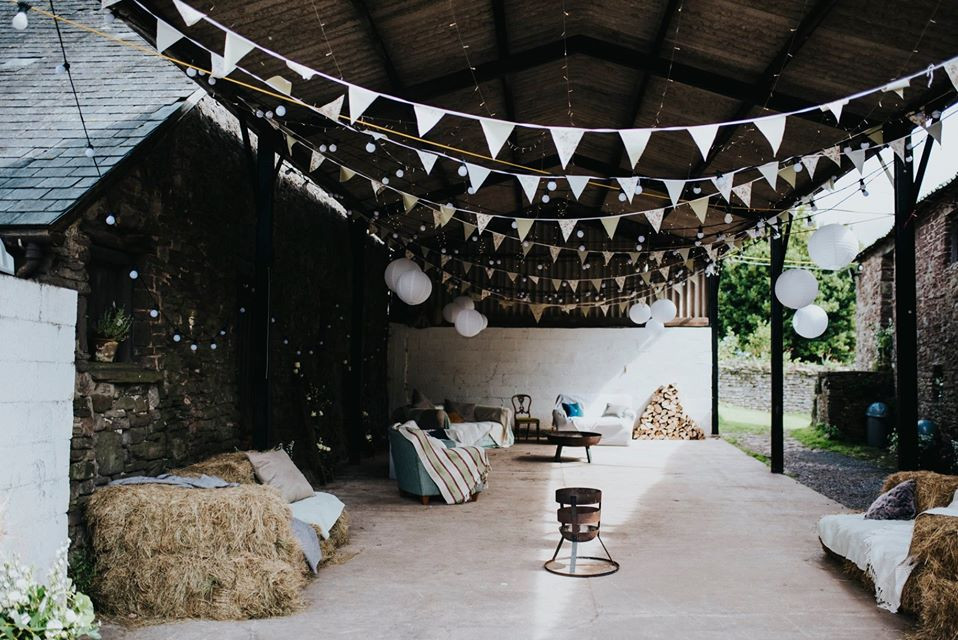 Open sided barn decorated for a wedding with bunting, festoon lights, sofa's, hay bale seating and fire pits.