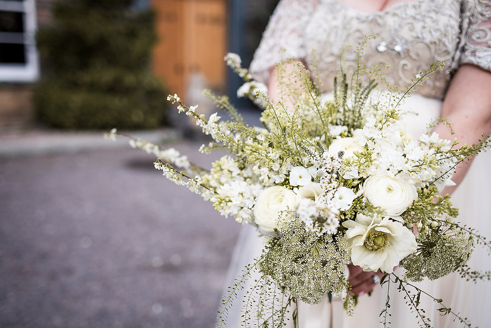 Close up of a wildflower spring wedding bouquet in limes and whites