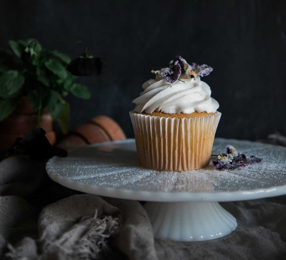 A single cup cake on a cake stand, topped with cream and edible purple flowers
