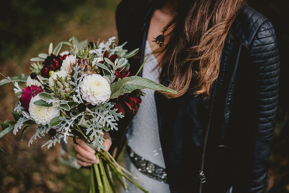 Bride holding an autumnal bridal bouquet in whites and deep reds. Bride is wearing a beaded wedding dress and a leather jacket.