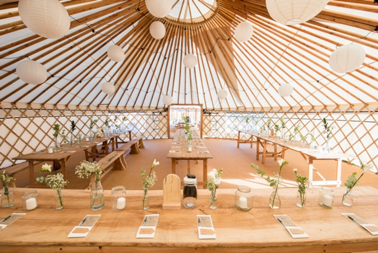 Inside a wedding yurt, there are long wooden rustic tables dressed wth white and green flowers in glass bottles.