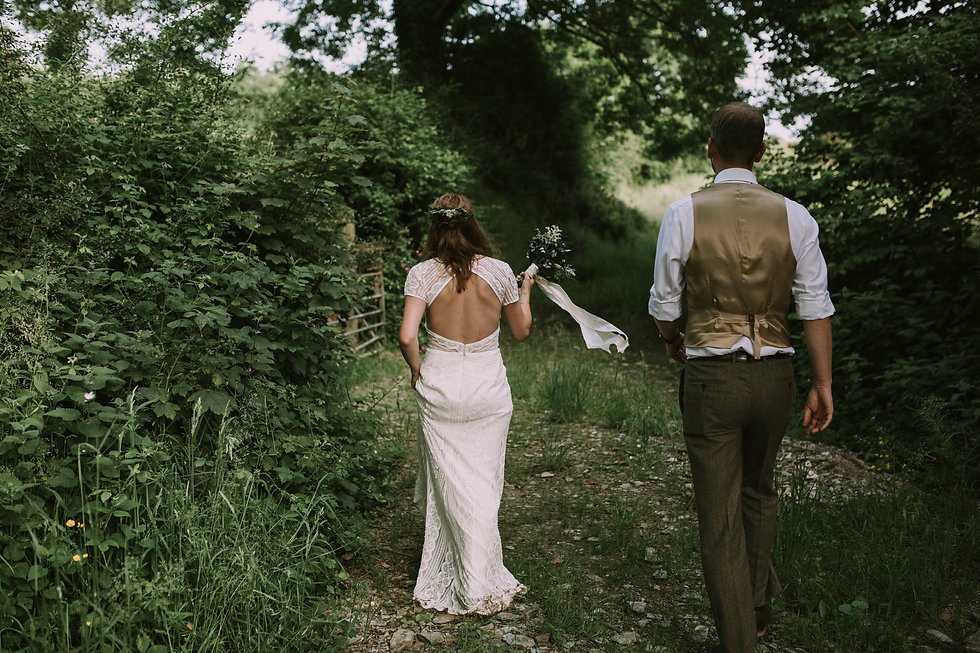 Bride and groom walking away down an overgrown path. Bride is carrying a green and white bouquet