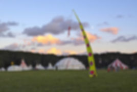 Festival field with a white dome and tipi's in the background and a tall yellow and red flag in the forground