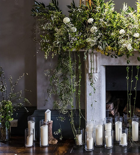 Marbel fireplace with a big green and white trailing floral display. There are lots of pillar candels in hurricane lamps on the floor