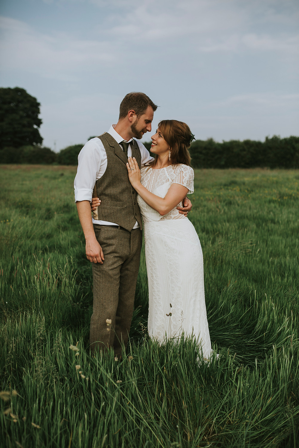 Bride and groom gazing into each others eyes in a grassy meadow. Groom is wearing a beige wool suit.
