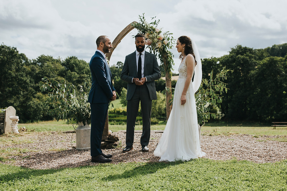 Outdoor wedding ceremony. Bride and from are facing each other with the celebrant facing the camera. There is a rustic wooden arch decorated with flowers and trees in the background.