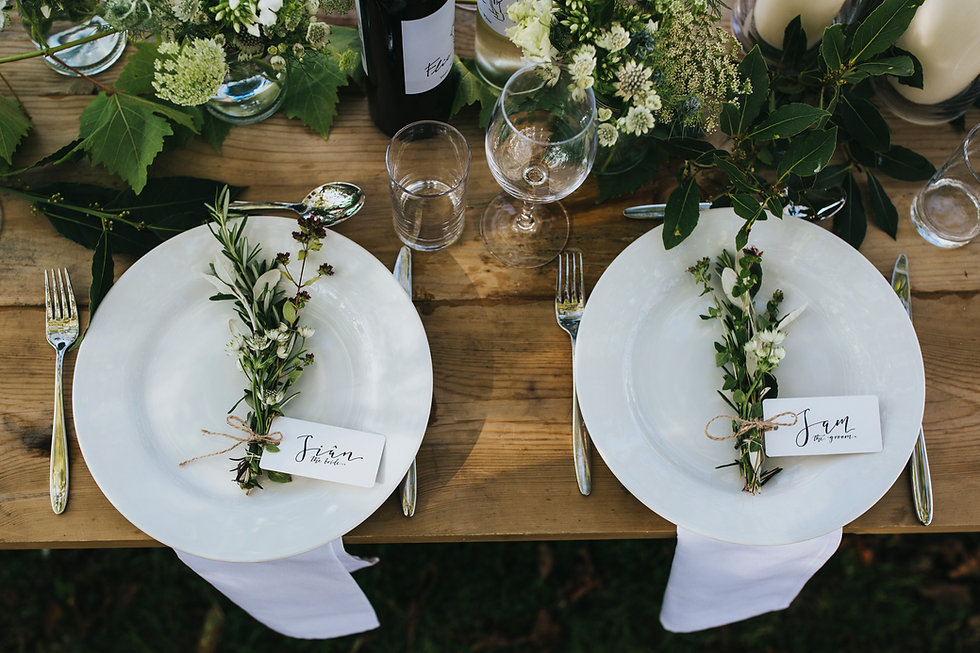 Rustic wooden table dressed with white plates with bunches of herbs and hand written bride and groom tags. There are green and white table flowers and a bay table runner.