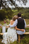 Bride and groom sitting with their backs to us at their wedding table in a meadow